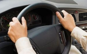 Close up of man's hands on steering wheel - traffic violation representation springfield