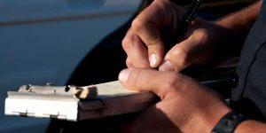 Officer Signing Traffic Ticket - Traffic ticket help Missouri
