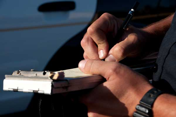 Officer Signing Traffic Ticket - Traffic ticket help Missouri