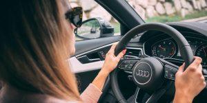 woman driving car in sunglasses