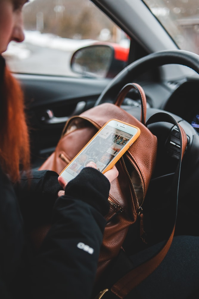 woman on her phone in car